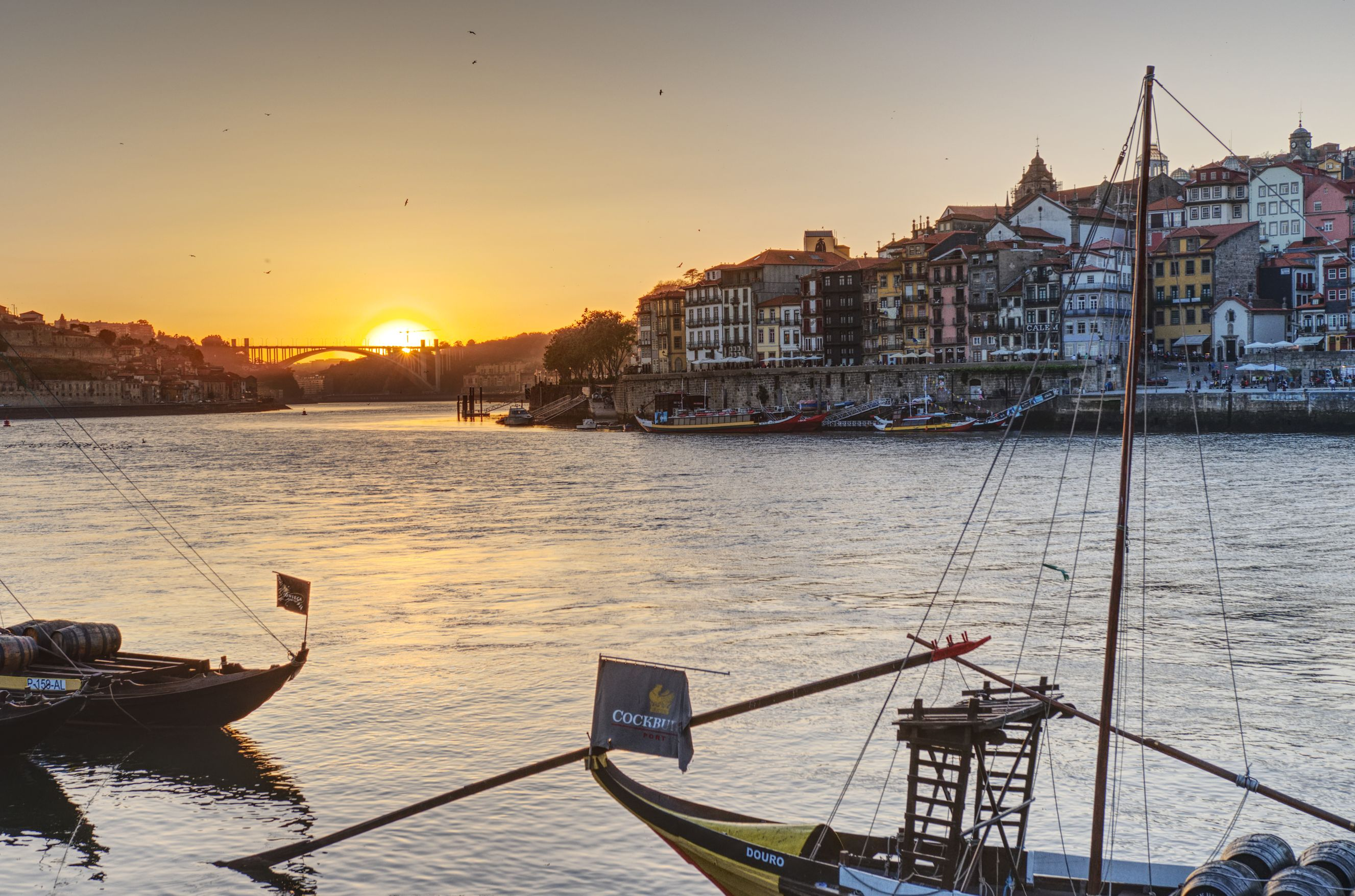 The sun goes down over the sea, in the foreground one of the Douro bridges of Porto