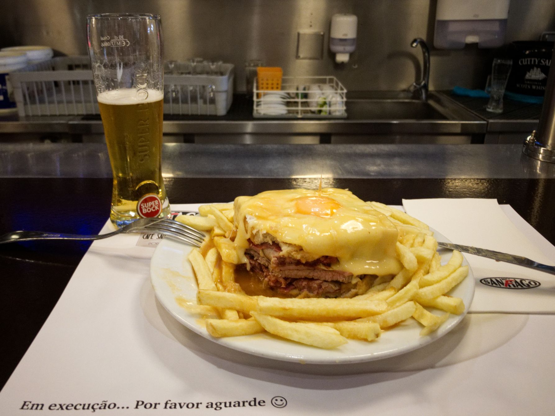 Three kinds of meat and sausage between toast slices and a fried egg gratinated with hearty cheese Café Santiago