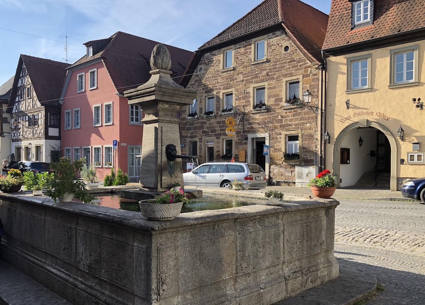 Brunnen im Zentrum von Prichsenstadt, im Hintergrund die Bäckerei