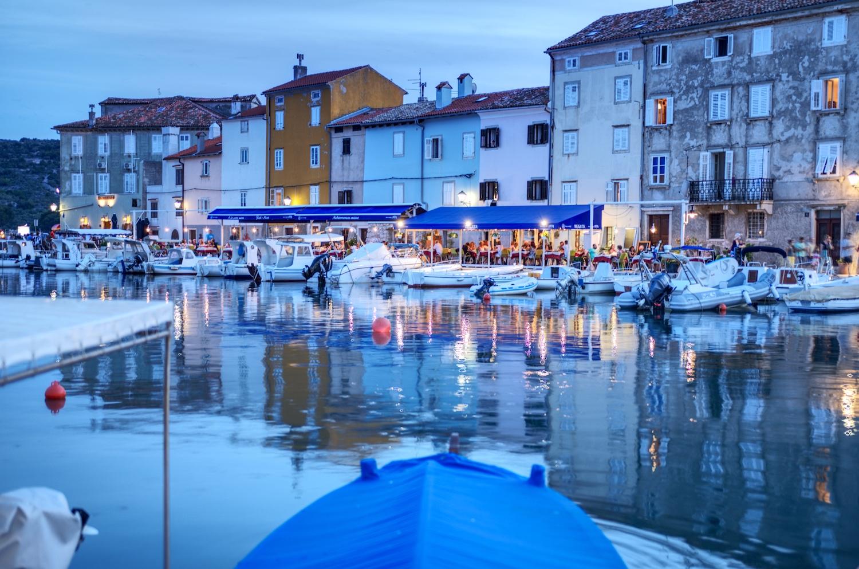 Gegen Abend füllen sich die Restaurants im Hafen und die Lichter spiegeln sich auf dem Wasser
