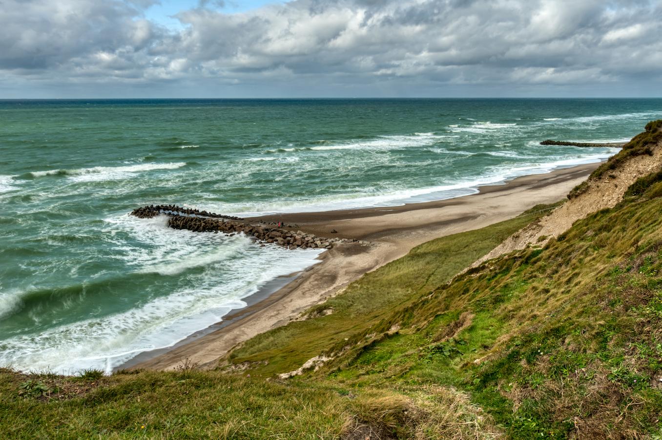 Wellen schlagen auf den Strand an der Steilküste von Bovbjerg