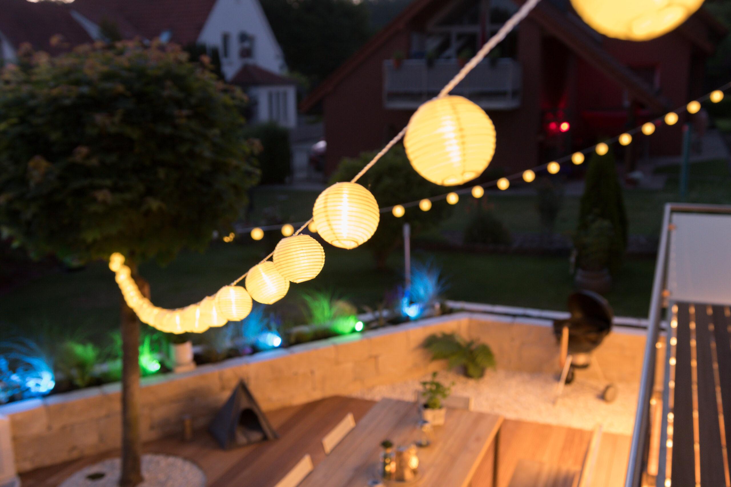 Die Outdoor-Lampion-Lichterkette wirft ein warmes Licht auf die Terrasse.