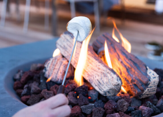 Roasting marshmallows at the fire table on the terrace