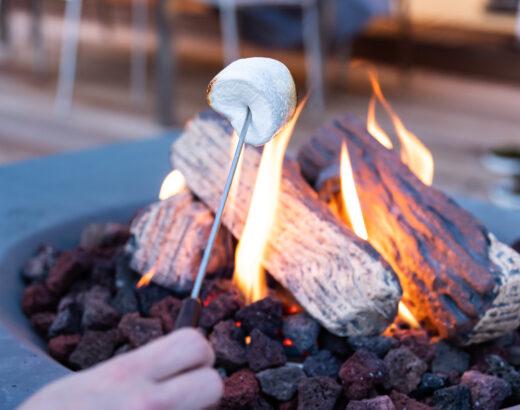 Marshmallows am Feuertisch auf der Terrasse rösten