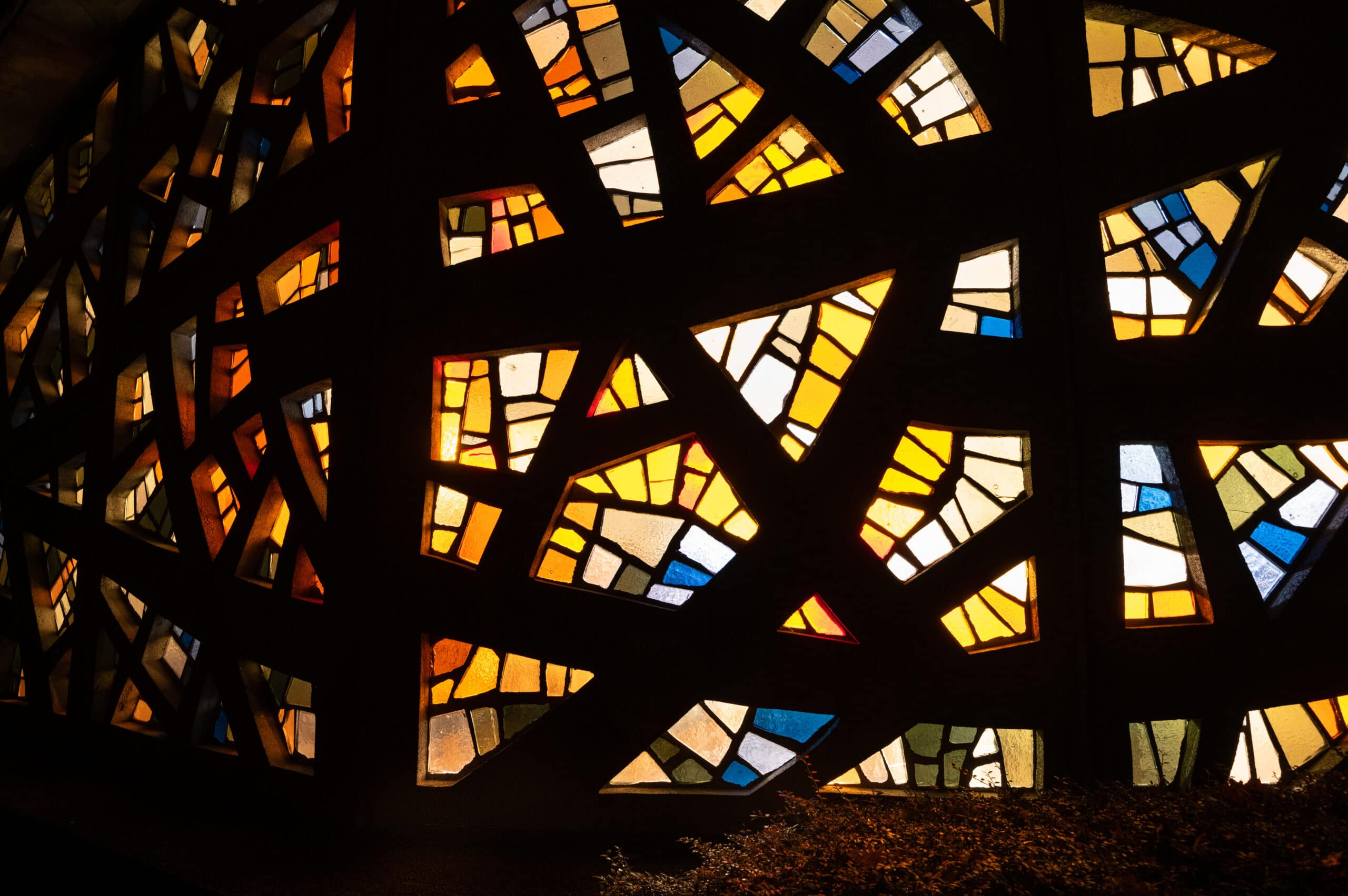 From inside, the lights shine through the colorful glass of the chapel.