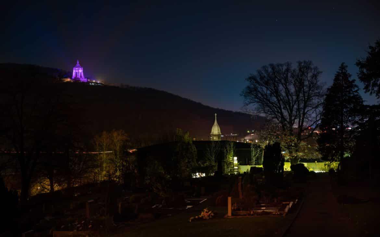 Kaiser-Wilhelm-Denkmal anlässlich des Welt-Brustkrebstages pink erleuchtet. Friedhof Hausberge und das Rathaus Porta Westfalica im Vordergrund.