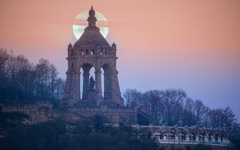 """Nahezu auf Augenhöhe: Monduntergang hinter dem Denkmal vom oberen Teil der """"Kempstraße"""" aus gesehen"""