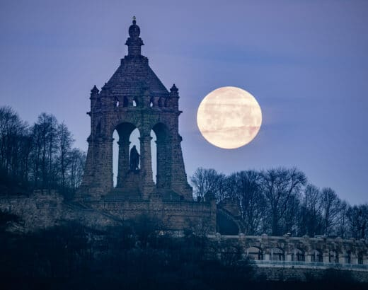 Full moon setting behind the Kaiser Wilhelm Monument in Porta Westfalica