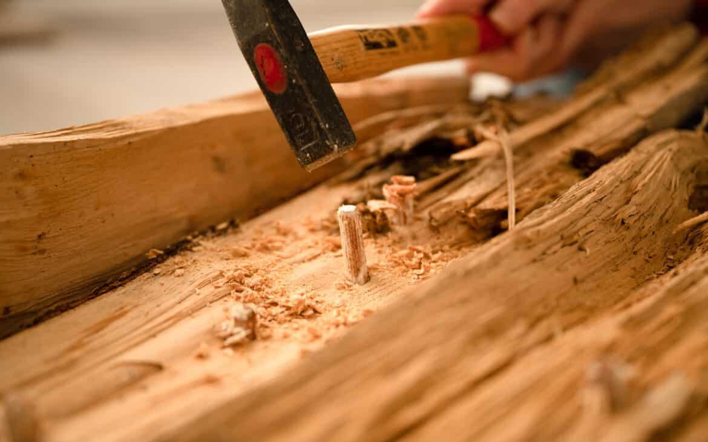 Die Pilzdübel werden in die Holzscheite geschlagen.